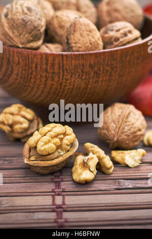 Walnuts in wooden bowl on wooden background - Stock Photo