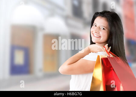 Woman carrying shopping bags, in a street - Stock Photo