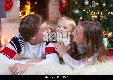 Happy family mother, father and baby little boy playing in the winter for the Christmas holidays - Stock Photo