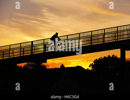 Person  in silhouette cycling over pedestrian footbridge with colour filled sunset sky behind. - Stock Photo