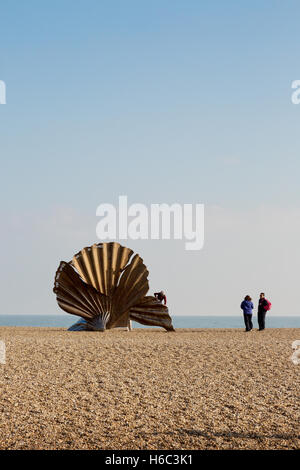 People looking at the Scallop sculpture by Maggi Hambling on Aldeburgh beach, Aldeburgh, Suffolk coast, England - Stock Photo