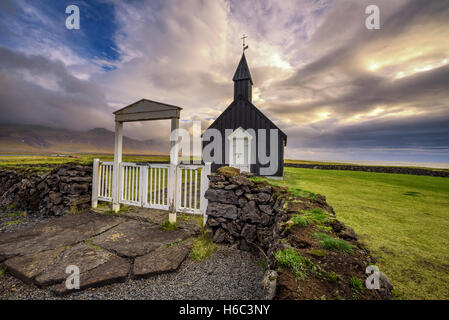Entry gate and black wooden church of Budir in Iceland - Stock Photo