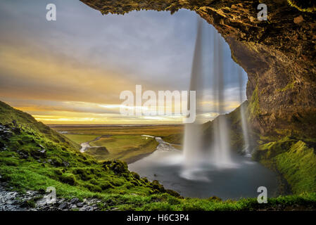Summer sunset over the famous Seljalandsfoss Waterfall  in Iceland  viewed from behind the fall. - Stock Photo
