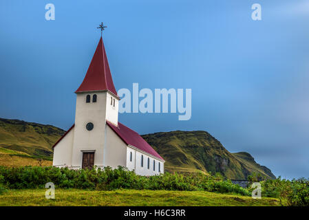 Heavy clouds over the lutheran church  on a mountain top in the town of Vik in Iceland. Long exposure. - Stock Photo