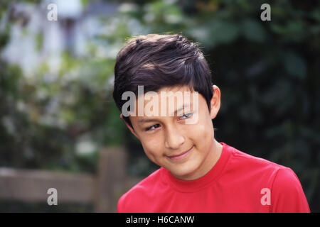 Portrait of smiling Hispanic young boy - taken with vintage lens - Stock Photo