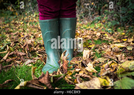 wellies in leaves - Stock Photo