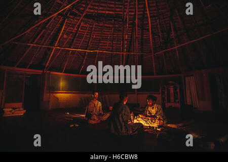 A man receives a cup of Ayahuasca, traditional Amazonian plant medicine used for visionary healing in a shipibo - Stock Photo