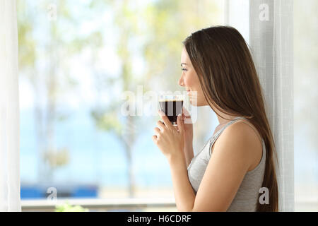 Side view portrait of a pensive girl drinking coffee and looking outdoors through a window of an hotel room - Stock Photo