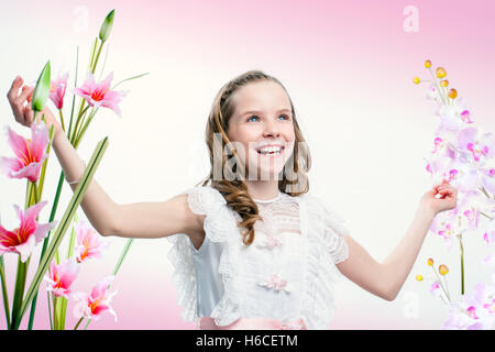 Close up portrait of happy young communion girl among flowers. - Stock Photo