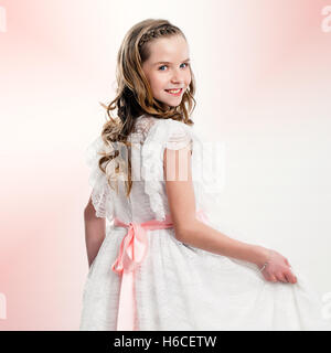 Close up studio portrait of cute girl in communion dress. - Stock Photo