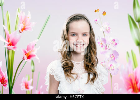 Close up portrait of young girl wearing communion dress in flower garden. - Stock Photo