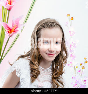 Close up beauty portrait of young girl in white communion dress among flowers. - Stock Photo