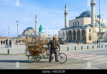 The man transporting the garbage in cargo cycle through the central square of the old town - Stock Photo