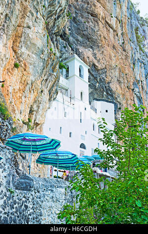 The upper church of Ostrog Monastery surrounded by rocks, Niksic, Montenegro. - Stock Photo