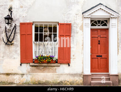 Charming Scene of a Window Decorated with Flowers and Wood Framed Door in the Charleston Historic District, South - Stock Photo
