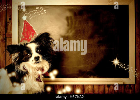 Funny dog Christmas greeting cards, little dog and Santa hat children's drawing in a blackboard with copy space - Stock Photo
