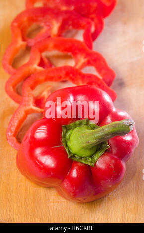 Red pepper cut byslice on a wooden background. Vertical photo - Stock Photo