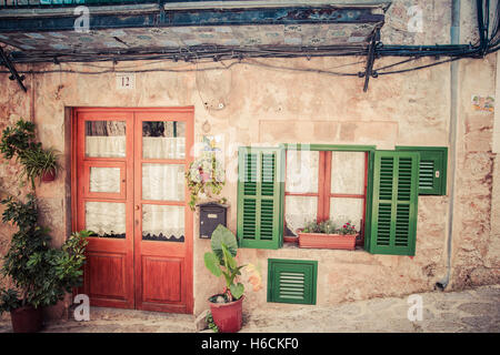 house facade with doors and green window on medieval street in valldemossa spain - Stock Photo