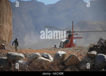a rescue helicopter removes an injured person from close to the village of Tangee in the mustang region of Nepal - Stock Photo