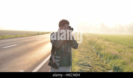Landscape professional photographer taking a picture near a road with the sunrise in the background - Stock Photo