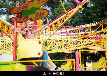 Senior couple having fun in amusement park - Stock Photo