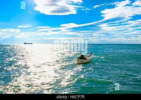 The old lonely boat in the waters of Aegan Sea near Thessaloniki promenade, Greece. - Stock Photo
