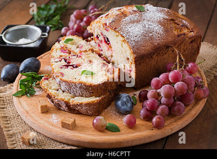 Juicy and tender cupcake with plums and grapes - Stock Photo