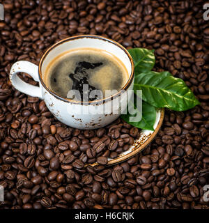 Black coffee with green leaves on caffee beans background. Vintage style toned picture - Stock Photo