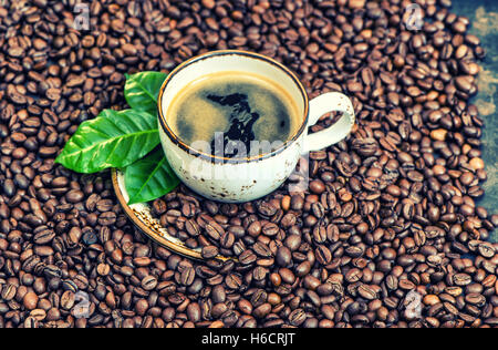 Black coffee with green leaves on coffee beans background. Vintage style toned picture - Stock Photo