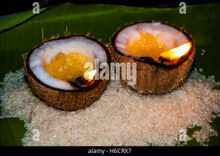 Offerings of rice and oil burning lamps in coconut shells, Srirangam, District Tiruchirappalli, Tamil Nadu, India - Stock Photo