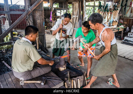 Local blacksmiths banging with hammers on glowing piece of metal, Inle Lake, Shan State, Myanmar - Stock Photo