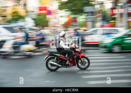 Scooter driver in heavy traffic, motion blur, Ho Chi Minh City, Vietnam - Stock Photo