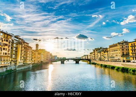 View of Ponte Santa Trinita bridge from Ponte Vecchio over Arno River, Florence, Tuscany, Italy - Stock Photo