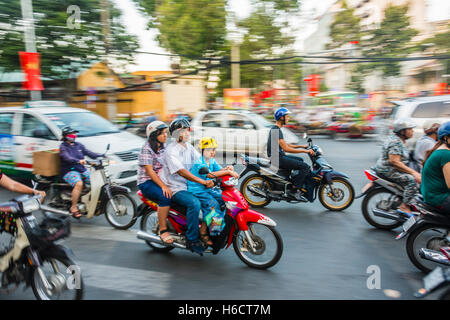 Family on a scooter in heavy traffic, motion blur, Ho Chi Minh City, Vietnam - Stock Photo