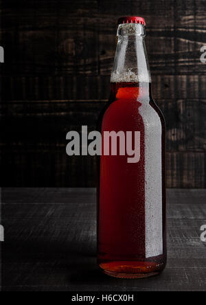 Bottle of brown ale beer with foam on wooden background - Stock Photo
