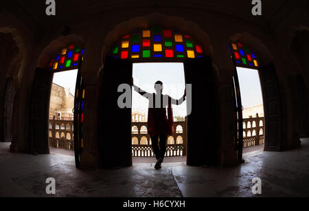 Woman with scarf in silhouette standing in arch with mosaic glass of Hawa Mahal, Rajasthan, India - Stock Photo