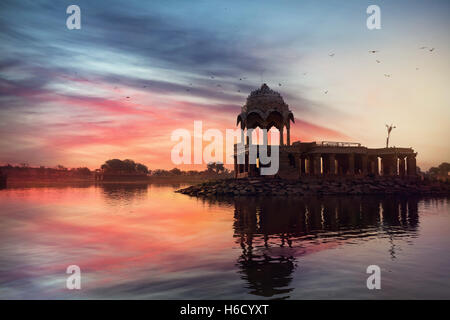 Silhouette of Temple on the Gadi Sagar lake at pink vibrant sunset sky in Jaisalmer, Rajasthan, India - Stock Photo