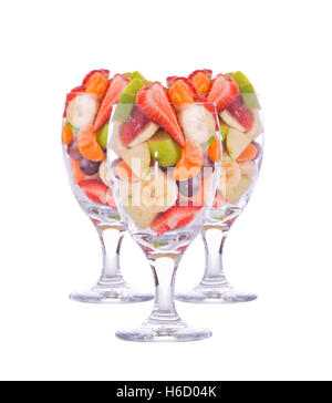 Three colorful, healthy fruit salads in a large glasses, isolated on white - Stock Photo