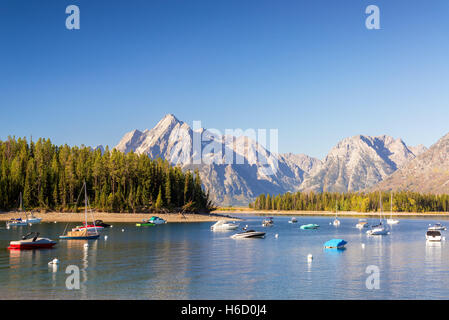 Boats in Colter Bay with the Teton Mountain Range in the background in Ground Teton National Park - Stock Photo
