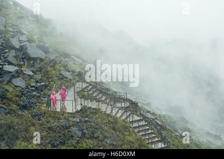 People in rain ponchos brave the mist and spray from the American Falls on the walk to the Crows Nest in Niagara - Stock Photo