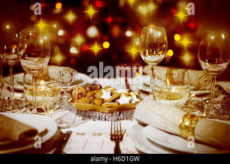 A festively laid table, in the background a colorful Christmas tree - Stock Photo