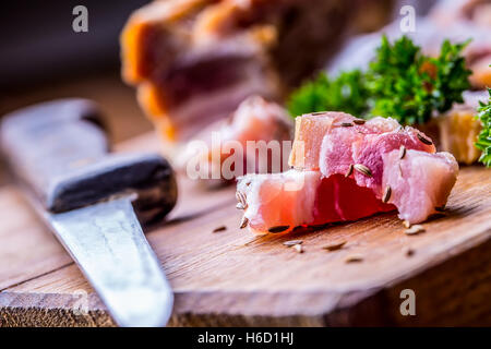 Raw smoked bacon slices on wooden board with cumin and herbs. - Stock Photo