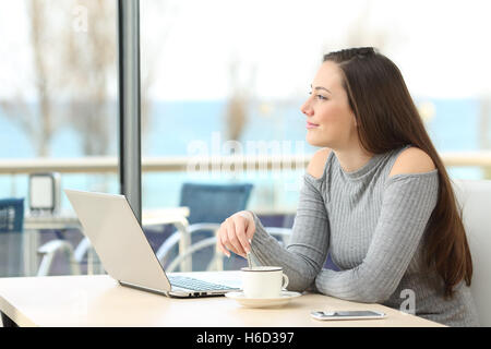 Happy pensive woman thinking and planning looking at horizon outdoors through a window in a bar with the sea in - Stock Photo