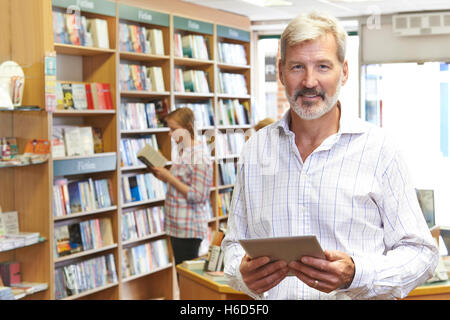 Portrait Of Male Booshop Owner Using Digital Tablet - Stock Photo
