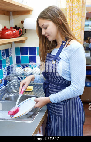Teenage Girl With Part Time Job Washing Up In Coffee Shop - Stock Photo