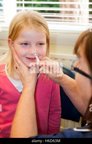 Six / 6 year old child receives dose of Fluenz flu vaccine nasal spray immunisation from NHS Practice nurse. UK. - Stock Photo