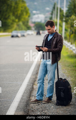 man standing with digital tablet waiting for car or taxi. Hitchhiking - Stock Photo