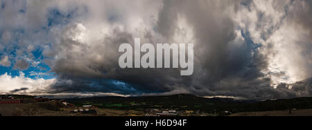 Panoramic view on Cumulus cloud which is growing over the city. Norway - Stock Photo