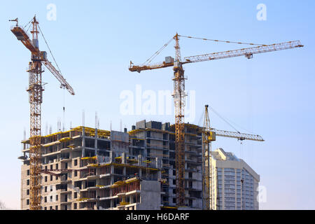 Building cranes and under construction building against the clear sky - Stock Photo