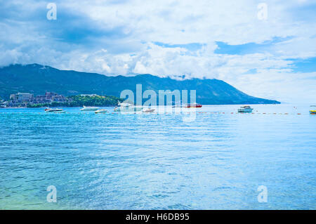 The coastline of the Budva riviera with the tourist boats and vilages of Becici and Rafailovici on the background - Stock Photo